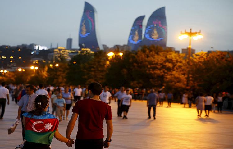 A girl, draped in Azerbaijan's national flag, walks with a boy on a street in downtown Baku, Azerbaijan on June 18, 2015. (Reuters/Stoyan Nenov)