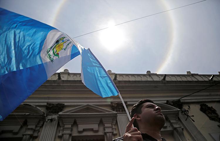 Um homem agita uma bandeira guatemalteca na Cidade da Guatemala, Guatemala, em 14 de setembro de 2017. (Reuters/Luis Echeverria)