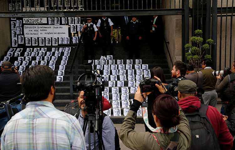 A photographer takes pictures of images of reporter Candido Rios, who was killed in Veracruz, during a demonstration against his killing, at the Interior Ministry building in Mexico City, Mexico on August 24, 2017. Last year, at least six reporters were murdered in Mexico in retaliation for their work, according to CPJ research.(Reuters/Henry Romero)