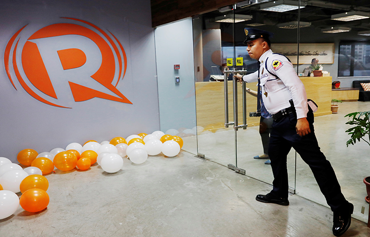 A guard opens a door at the office of Rappler in Pasig, Metro Manila, Philippines on January 15, 2018. (Reuters/Dondi Tawatao)