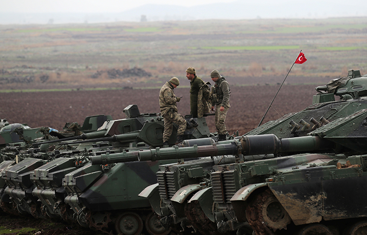 Turkish army tanks and armored personnel carriers are seen near the Turkish-Syrian border in Hatay province, Turkey on January 23, 2018. (Reuters/Umit Bektas)