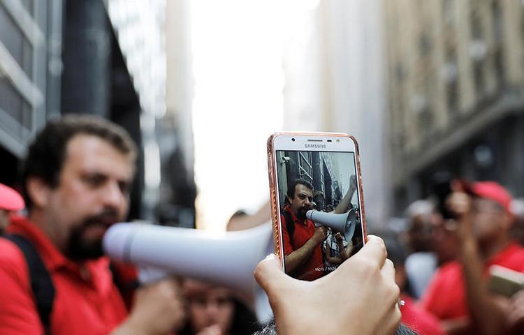 Um telefone celular é usado para filmar um protesto de desabrigados em São Paulo em dezembro de 2017. Antes das eleições de outubro, a polícia é encarregada de combater a proliferação de notícias falsas. (Reuters / Nacho Doce)