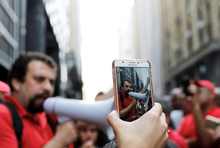 A cell phone is used to film a homelessness protest in Sao Paulo in December 2017. Ahead of October elections, police are tasked with combating the spread of fake news. (Reuters/Nacho Doce)