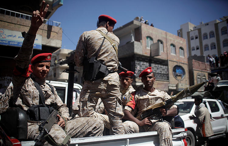 Military police ride on the back or a patrol truck as they secure a road where people held a ceremony commemorating the anniversary of the 2011 uprising that toppled Yemen's former president Ali Abdullah Saleh in Taiz, Yemen in February 2018. Yemeni authorities detained Awad Kashmeem, the former governor of the board of directors for the government-aligned newspaper November 30, in Mokalla, Hadramout Province, according to news reports. (Reuters/Anees Mahyoub)