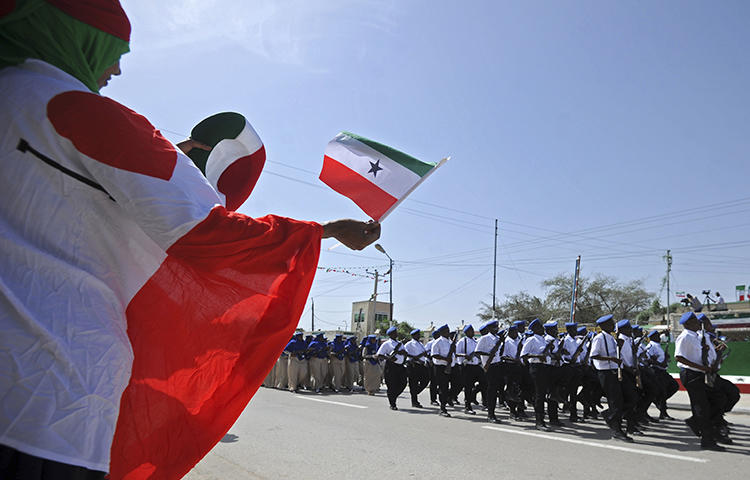 People wave flags as soldiers and other military personnel of Somalia's breakaway territory of Somaliland march past during an Independence day celebration parade in the capital, Hargeisa on May 18, 2016. Somaliland authorities detained journalist Mohamed Aabi Digaale on February 17, 2018. (Mohamed Abdiwahab/AFP)
