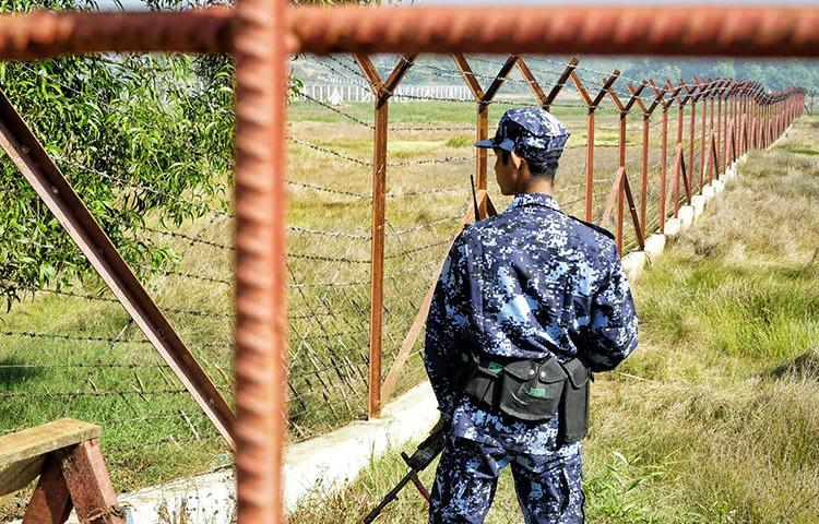 A Myanmar border guard stands next to fencing near Maungdaw, Rakhine state, where structures to process Rohingya refugees are being built. Local and international journalists face challenges reporting on the crisis and other politically sensitive issues. (AFP/Cape Diamond)