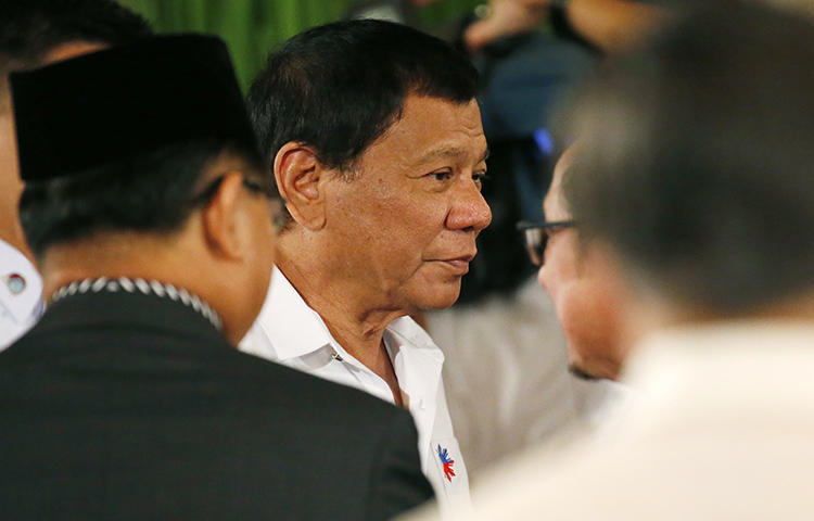 Philippine President Rodrigo Duterte, center, before he addresses Filipino Muslim leaders during a reception at the Presidential Palace to celebrate the end of the Holy Month of Ramadan in June 2017. Presidential spokesperson Harry Roque told local media the government decided to ban Rappler from covering official presidential events because Duterte had