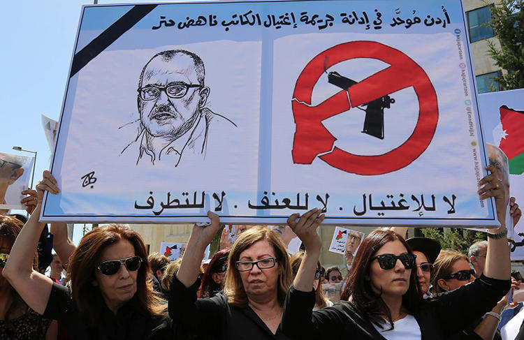 Relatives of Nahed Hattar carry signs condemning his murder during a protest in Amman in September 2016. The Jordanian commentator and writer was shot dead outside a court while on trial for blasphemy over a Facebook cartoon. (AP/Raad Adayleh)