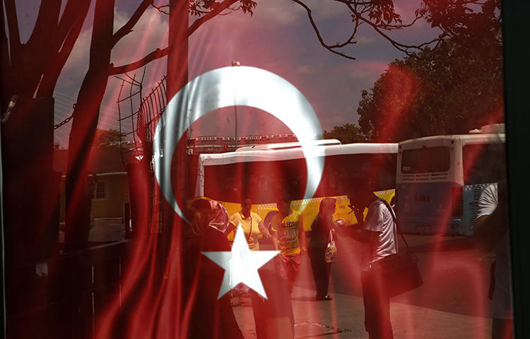 People reflected on glass with Turkish a flag at a bus station in Istanbul in July 2016. A proposed bill presented to Turkey's parliament on February 2 would force online broadcasters, including YouTube and Netflix Turkey, to be licensed and regulated by the federal TV and radio watchdog group RTÜK, according to local reports. (AP/Petros Karadjias)