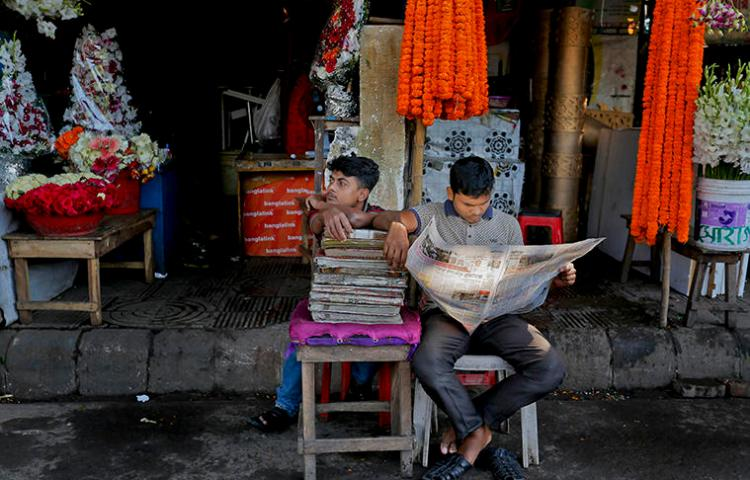 A man reads a newspaper outside a Dhaka flower stall in 2015. Bangladesh's press say a climate of fear amid legal action, attacks, and threats makes covering sensitive issues difficult. (AP)