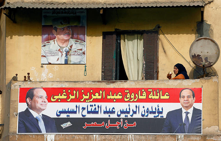"In Cairo, Egypt, a woman sips on a cup of tea as she sits behind a poster of Egypt's President Abdel Fattah al-Sisi, who will run for a second term in an upcoming election. The poster reads ""We've chosen you for a second term"". (Reuters/Mohamed Abd El Ghany)"