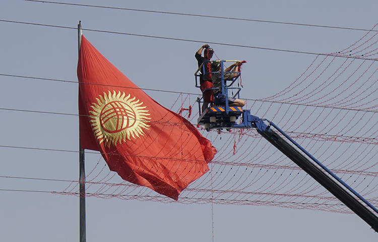Workers set up street decorations in front of the national flag in Bishkek, Kyrgyzstan in September 2017. Kyrgyz authorities charged freelance journalist Elnura Alkanova with seeking and disclosing confidential commercial information following the publication last fall of investigative reports on the allegedly corrupt sale of government property near the capital Bishkek, the independent online news site 24.kg reported. (Reuters/Shamil Zhumatov)