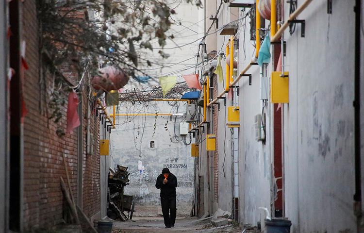 A man walks through an alley between residential houses in Hebei province, China in December 2017. Picture taken December 7, 2017. A group of men assaulted and robbed two television journalists while they were reporting on allegations of industrial pollution in the province in late January 2018. (Reuters/Thomas Peter)