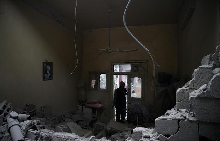 A man inspects a damaged house in the besieged town of Douma in eastern Ghouta in Damascus, Syria, on February 22, 2018. Eastern Ghouta has been under constant shelling, airstrikes, and rocket fire from al-Assad forces and their allies since February 18, 2018 to the date of publication, according to news reports. (Reuters/Bassam Khabieh)