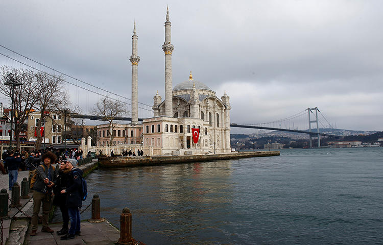 People take souvenir photos along the Bosphorus in Istanbul, Turkey in February 2018. Turkey continues to crackdown on the press; a Turkish court sentenced four journalists to life without parole on February 16, 2018, on charges relating to their journalistic activity. (Reuters/Osman Orsal)