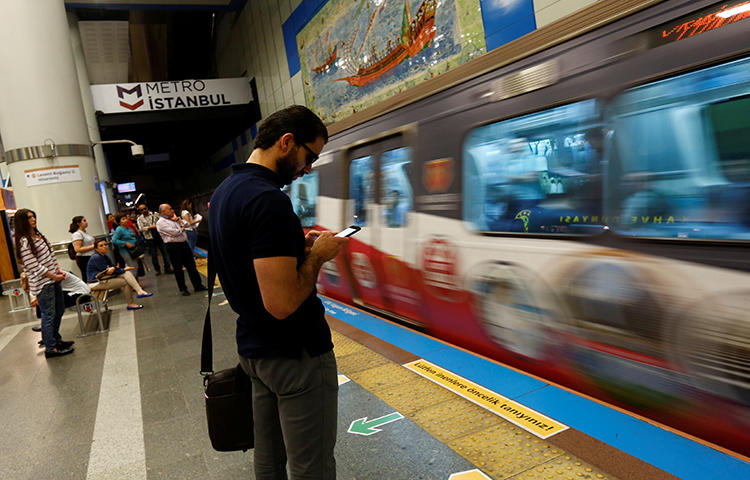 A passenger uses his smartphone as he waits for the train at a subway station in Istanbul, Turkey in June 2017. Turkey's parliament on February 21, 2018, approved an article of a bill that, if made into law, would give new censorship powers to state regulators. (Reuters/Murad Sezer)