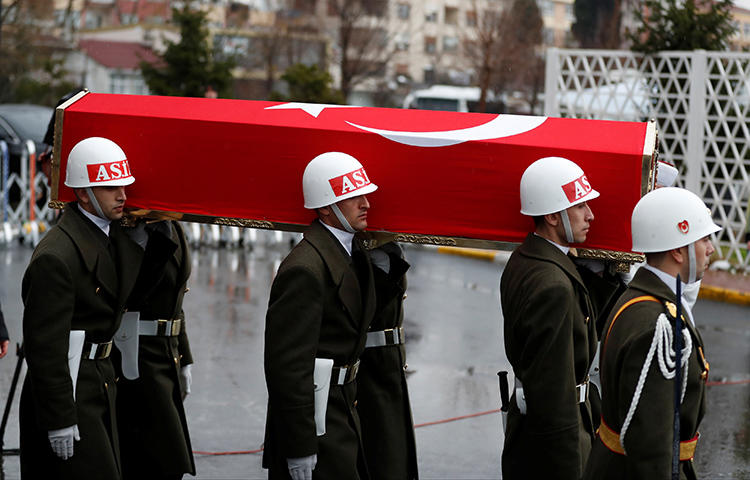 The flag-wrapped coffin of a Turkish soldier who was killed during the operation against Syria's Afrin region, is carried by guard of honor members during his funeral ceremony in Istanbul, Turkey in February 2018. Yusuf Ozan, a morning news host for the Islamist Akit TV channel, said journalists with the daily Cumhuriyet should be