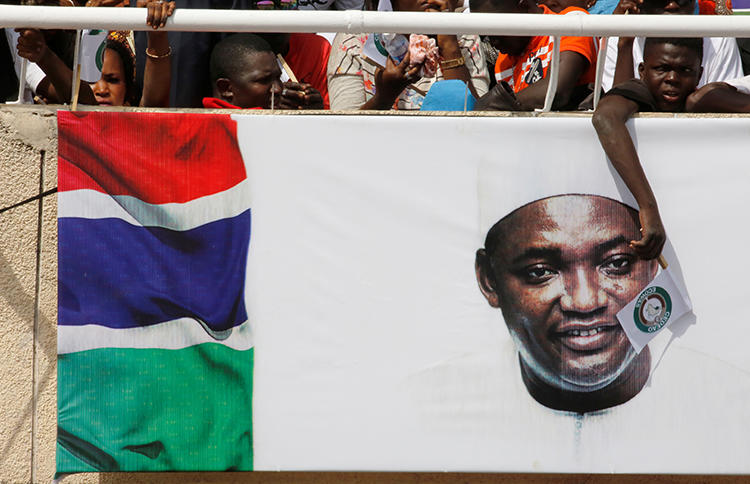 A supporter of Gambia's President Adama Barrow waves an ECOWAS flag at his swearing-in ceremony in February 2017. An ECOWAS court ruling calls on Gambia to repeal its criminal libel and false news laws. (Reuters/Thierry Gouegnon)