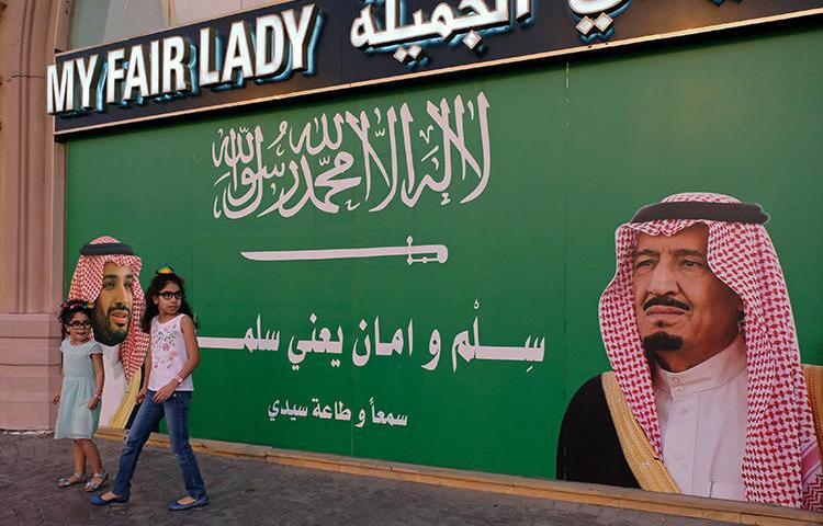 A poster in Jeddah depicts Saudi Arabia's King and Crown Prince. A Saudi court has jailed a journalist for five years for insulting the royal court. (Reuters/Reem Baeshen)