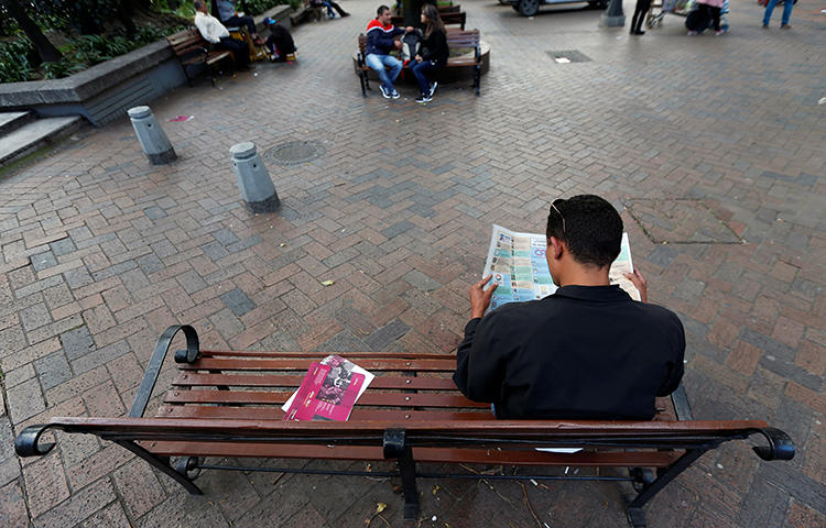 A man reads a newspaper in a park in Bogota, Colombia in January 2018. A Colombian court on February 1 sentenced the gunman responsible for the 2015 murder of Colombian radio journalist Luis Antonio Peralta Cuéllar and his wife Sofía Quintero. (Reuters/Jaime Saldarriaga)
