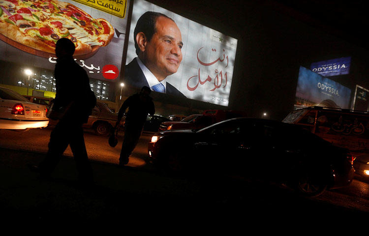 People walk near a billboard showing a picture of Egyptian President Abdel Fattah al-Sisi during the presidential election in Cairo, Egypt, March 28, 2018. During the election, Egyptian authorities blocked news sites and threatened journalists with retaliatory measures, according to reports. (Reuters/Amr Abdallah Dalsh)