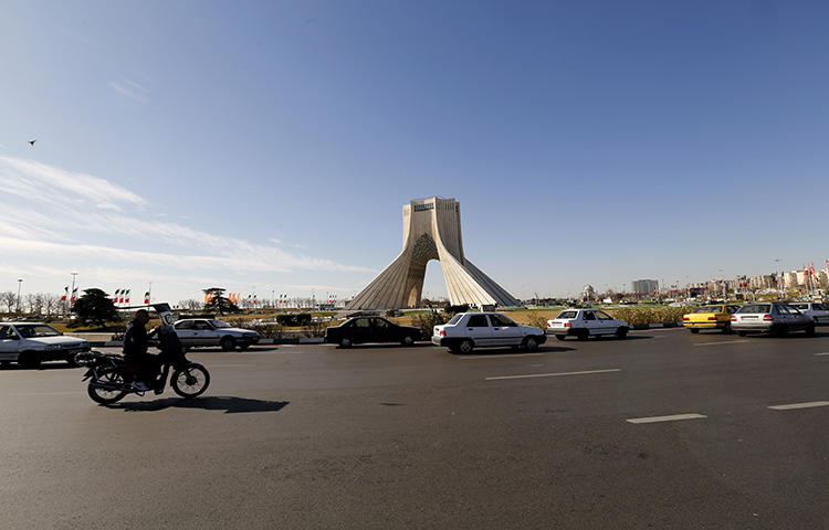 Iranian motorists drive past the Azadi Tower in the capital Tehran in January 2018. Iranian security forces on February 19 arrested Reza Entessari and Kasra Nouri, reporters with the Sufi news website Majzooban-e-Noor, while they were covering the violent dispersal of religious protests in Tehran, according to news reports. (AFP/Atta Kenare)