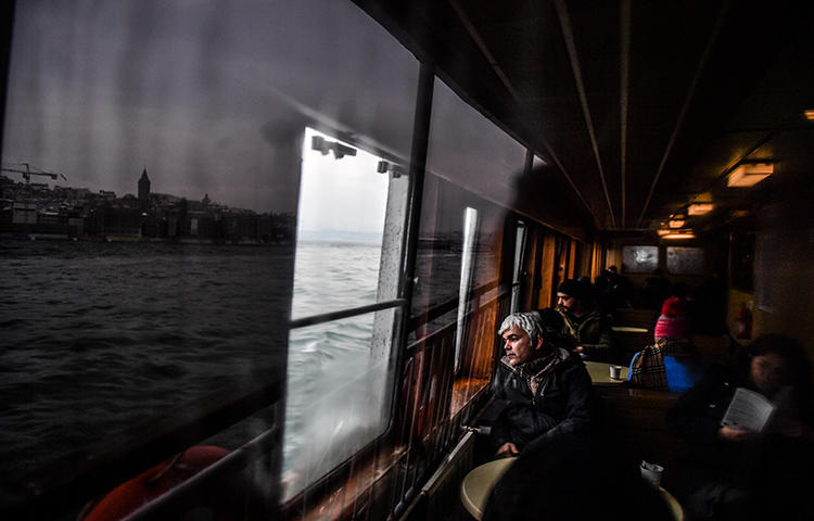 People look at the Bosphorus as they travel in a ferry from the Asian to the European side of Istanbul on March 1, 2018. The Turkish government continues its crackdown on the media. (AFP/ Bulent Kilic)