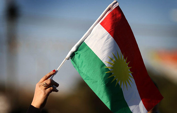 A Syrian Kurd waves the Kurdish flag in Erbil in Kurdish-controlled northern Iraq. Kurdish security forces have attacked and detained journalists covering protests against austerity measures taken by the Kurdistan Regional Government, according to news reports. (AFP/Safin Hamed)