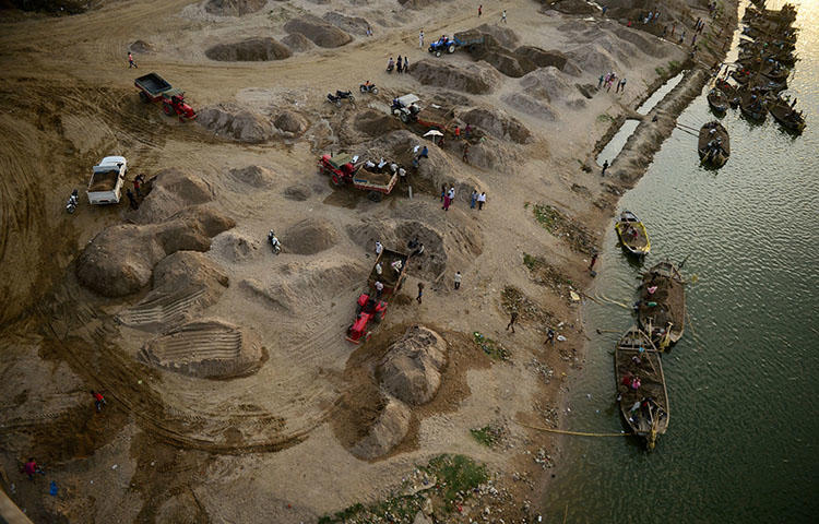 "Indian workers use boats to transport sand as they remove it from the River Yamuna in Allahabad in March 2018. Amid growing outrage over the latest murder of a journalist in India, police have arrested a truck driver accused of killing Sandeep Sharma over his investigative reporting into the country's ""sand mafia."" (AFP/Sanjay Kanojia)"