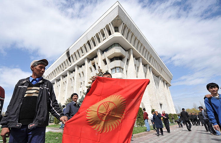 A man holds the Kyrgyz flag in front of the government building in Bishkek in April 2010. CPJ has joined calls for the Kyrgyz authorities to end the repressive climate for the country's press. (AFP/Vyacheslav Oseledko)
