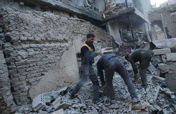 Members of the Syrian civil defense forces known as White Helmets search for victims following an airstrike in Arbin, eastern Ghouta on February 9, 2018. An airstrike on March 12 killed Arbin Unified Media Office photographer Bashar al-Attar. (AFP/Abdulmonam Eassa)