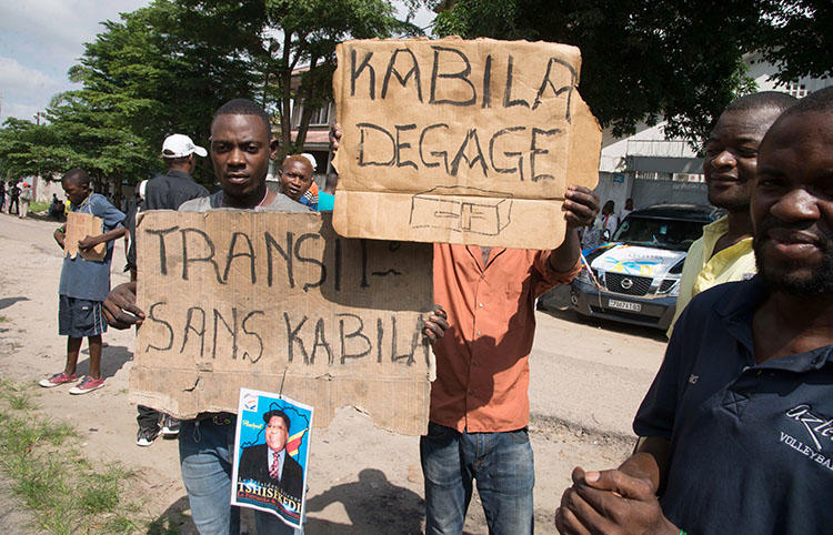 Opposition supporters hold placards reading 'Kabila - get lost' and 'Transition without Kabila' during a protest in Kinshasa on November 30, 2017. At least six local journalists were detained while trying to cover protests across the DRC. (AFP/Junior Kannah)