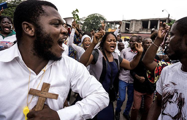 Catholics sing and dance during a December 31, 2017 demonstration to call for the President of the Democratic Republic of the Congo to step down. At least three journalists covering the rallies in Kinshasa say police harassed them. (AFP/John Wessels)