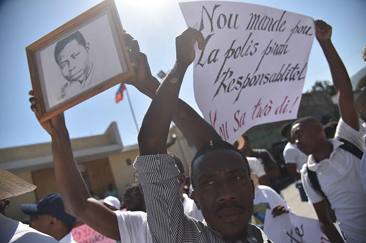 Haitian reporters and others march through the streets of Port-au-Prince on March 28, asking for information about missing freelance photojournalist Vladimir Legagneur. (AFP)