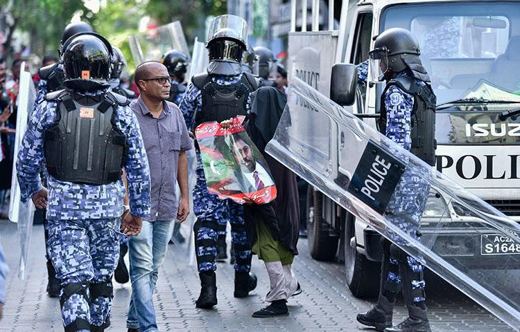 Maldivian police pictured at a protest in the capital, Malé, on March 2. Three Raajje TV journalists are detained over their coverage of anti-government protests held on March 16. (AFP/Ahmed Shurau)