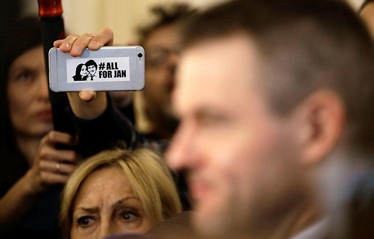 A journalist holds a phone with a sticker commemorating the assassinated Slovakian journalist Jan Kuciak, as Slovak deputy Prime Minister Peter Pellegrini talks to the media after a meeting at the presidential palace in Bratislava on March 15, 2018. (REUTERS/David W. Cerny)