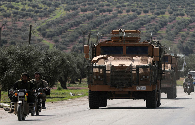 Turkish-backed Free Syrian Army members ride on a motorbike near a Turkish military vehicle in Afrin, Syria on March 19, 2018. Turkish forces and FSA factions seized Afrin from the Kurdish People's Protection Union (YPG) on March 18 after a two-month offensive, news reports stated. (Reuters/Khalil Ashawi)