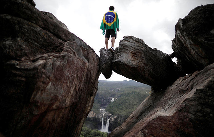 A park visitor wrapped in a Brazilian flag stands above a natural rock window in Chapada dos Veadeiros National Park in Alto Paraiso, Brazil in March 2018. At least one unidentified gunman on March 25 fired at the offices of the weekly Jornal dos Bairros, according to reports. (Reuters/Ueslei Marcelino)