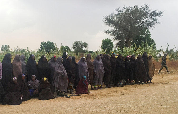 A man carrying a flag for the militant group Boko Haram walks past a group of 82 Chibok girls, who were held captive for three years by the militants, as the girls wait to be released in exchange for several militant commanders, near Kumshe, Nigeria on May 6, 2017. Nigeria's domestic intelligence agency has detained journalist Tony Ezimakor fin relation to an article he wrote about the release of the Nigerian schoolgirls, according to media reports. (Reuters/Zanah Mustapha)