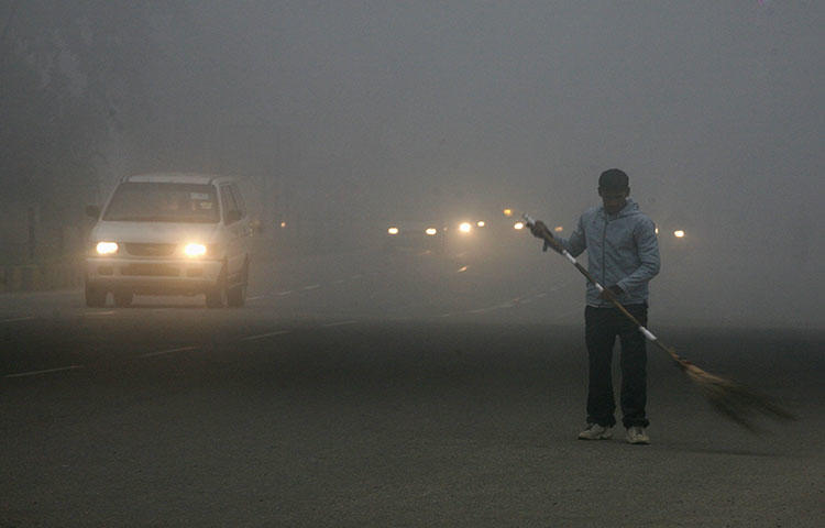 A sweeper cleans a busy road in India's capital New Delhi in January 2011. Two journalists in Bihar state died after a car ran them over on March 25, according to reports. (Reuters/Parivartan Sharma)