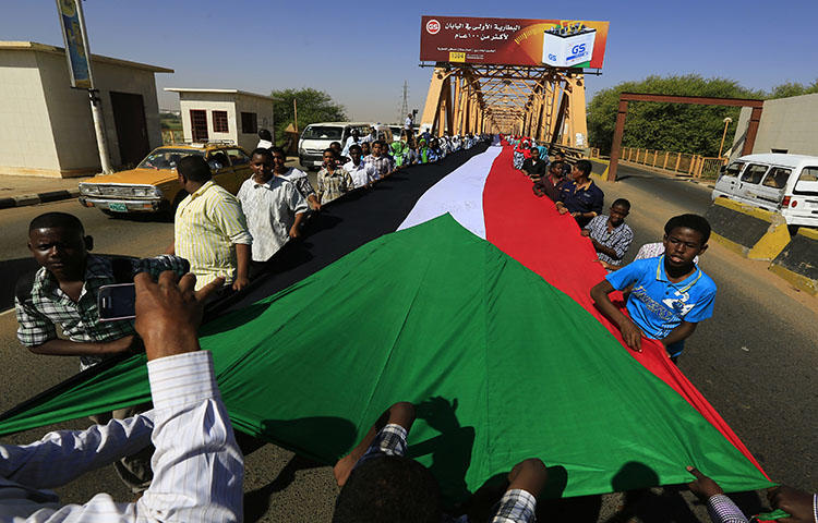 "Students carry Sudan's national flag during celebrations to mark Sudan's 59th Independence Day, in Khartoum January 1, 2015. Sudanese authorities sentenced two journalists to prison on ""false news"" charges on March 22, 2018, according to reports. (Reuters/Mohamed Nureldin Abdallah)"