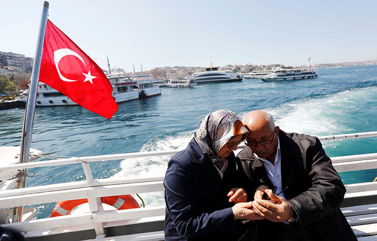 A couple check their mobile phone as they travel in a ferry in Istanbul, Turkey in April 2017. An Istanbul court on March 8, 2018, sentenced at least 22 journalists to prison on terrorism-related charges, according to news reports. (Reuters/Murad Sezer)
