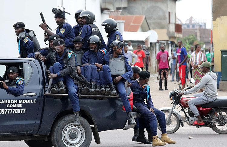 Police sit in a vehicle in front of Notre Dame Cathedral in Kinshasa, on February 25, 2018. Amid protests called by the Catholic Church, the DRC Telecommunications Ministry repeatedly orders internet and SMS shutdowns. (Reuters/Goran Tomasevic)
