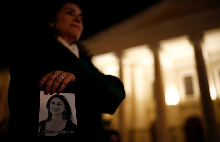 A woman holds a photo of Daphne Caruana Galizia at a memorial for the murdered journalist outside the Courts of Justice in Valletta, Malta, in February 2018. Three people are on trial in connection to her murder. (Reuters/Darrin Zammit Lupi)