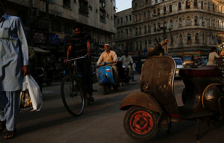 A man rides a scooter on a busy street in Karachi, Pakistan in March 2018. The privately owned Pakistani television channel Geo TV is not accessible throughout parts of the country including Karachi, according to reports.(Reuters/Akhtar Soomro)