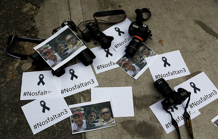 Colombian photographers leave the cameras on the floor in front of the Ecuadorean embassy in Bogota, Colombia, on April 16, 2018, to protest against the murder of journalist Javier Ortega, photographer Paul Rivas and their driver Efrain Segarra, (Reuters/Jaime Saldarriaga)