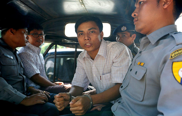 Detained Reuters journalist Kyaw Soe Oo and Wa Lone are transported in a police vehicle after a court hearing in Yangon, Myanmar on April 20, 2018 . (Reuters/Ann Wang)