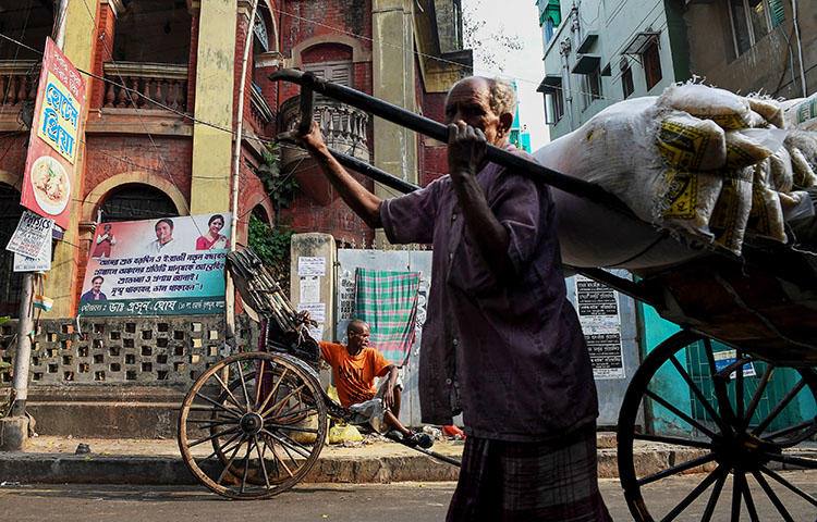 An Indian rickshaw puller waits for commuters as another rickshaw transports goods in Kolkata, India on March 12, 2018. Biplab Mondal, a photojournalist with the Times of India Kolkata city bureau, and Manas Chattopadhyay, a reporter with the regional ETV Bharat television channel, were attacked while covering elections in West Bengal, India. (AFP/Dibyangshu Sarkar)