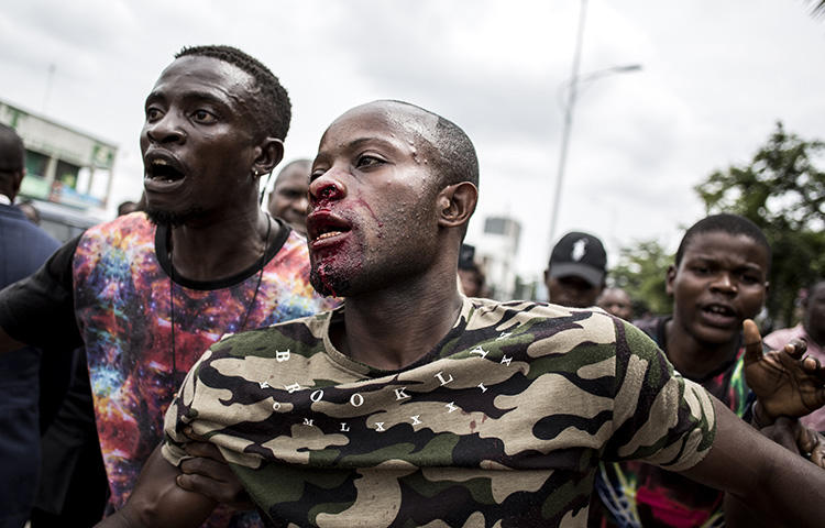 An injured man is pulled to safety after police fired warning shots to disperse a crowd at the end of a service to commemorate the victims of a crackdown on a march in Kinshasa in December 2018. (AFP/John Wessels)
