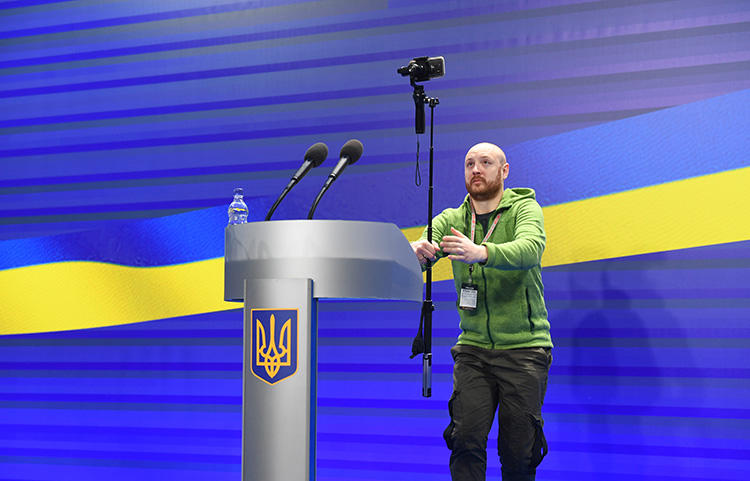 A journalist films before a presidential press conference in Kiev on February 28, 2018. A Kiev prosecutor is refusing to return the passport of Turan TV's correspondent Fikret Huseynli. (AFP/Sergei Supinsky)